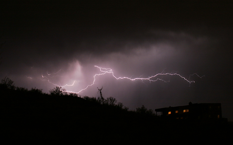 Lightning over a house on a hill in Tucson, Arizona