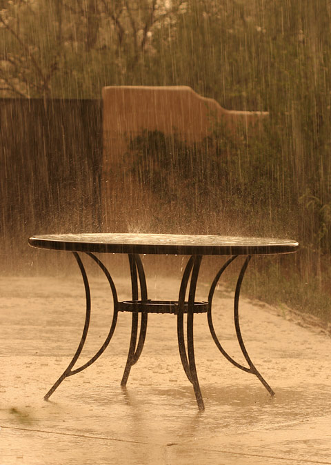 Heavy rain pounding on a table at sunset