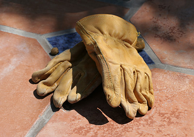 Old leather gloves on a tiled bench